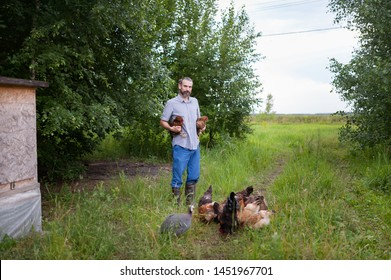 A young female farmer holds two chickens in his hands. A bearded man stands outdoor on a background of green trees next to a small chicken coop, and near his feet are fed hens rooster and Guinea fowl