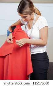 Young female fashion designer adjusting pins on a red fabric draped on mannequin