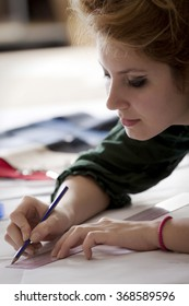 Young female fashion designer or student is designing and sketching her new dress for homework.