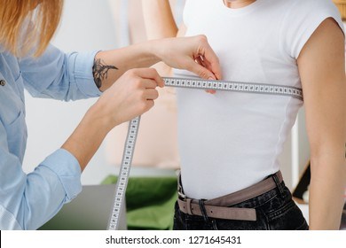 Young female fashion designer taking measurements of a woman to design new clothes. She measuring breast. Cropped photo. Hands. No face.