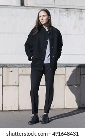 young female fashion model in black bomber jacket, gray shirt and black boots - street style
