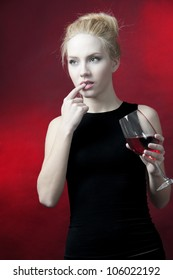 young female fashion model holding wine glass full of red wine at red background