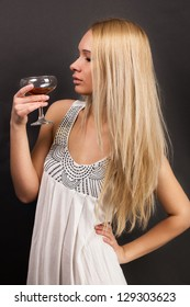 young female fashion model holding wine glass full of red wine
