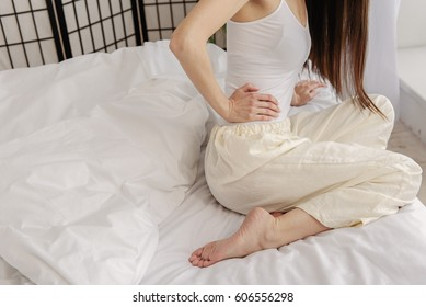 Young female feeling pain in bed