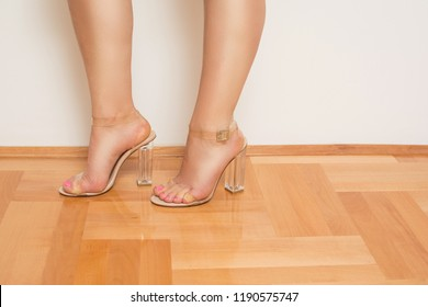 Young female feet in transparent sandals. Modern female high heel see-trough shoes. Studio lighting, medium retouch.