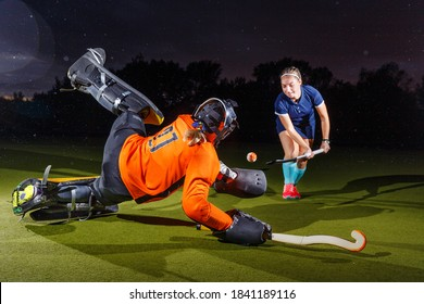 Young female field hockey player attacking the goalkeeper. Goalie defense the net in jump