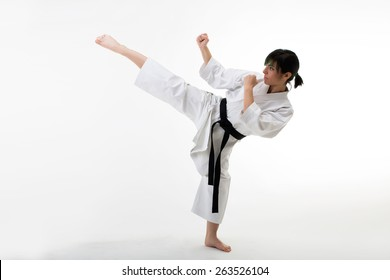 Young female fighter training karate hight kick . Isolated on white background