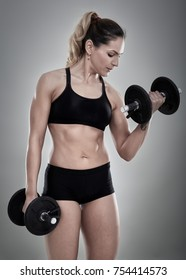 Young female fitness model doing biceps curl with dumbbells