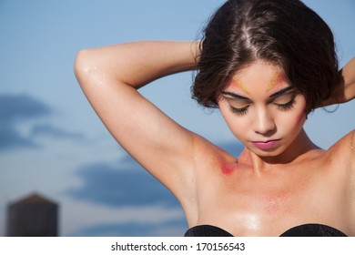 young female fixing hair with a sky background