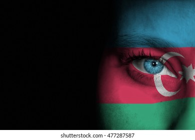 A young female with the flag of Azerbaijan painted on her face on her way to a sporting event to show her support.