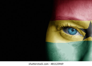 A young female with the flag of Ghana painted on her face on her way to a sporting event to show her support.