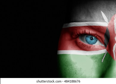 A young female with the flag of Kenya painted on her face on her way to a sporting event to show her support.