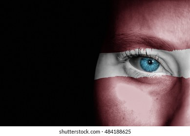 A young female with the flag of Latvia painted on her face on her way to a sporting event to show her support.