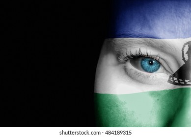 A young female with the flag of Lesotho painted on her face on her way to a sporting event to show her support.