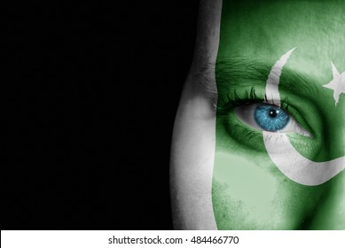 A young female with the flag of Pakistan painted on her face on her way to a sporting event to show her support.