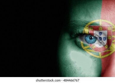 A young female with the flag of Portugal painted on her face on her way to a sporting event to show her support.