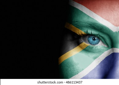 A young female with the flag of South Africa painted on her face on her way to a sporting event to show her support.