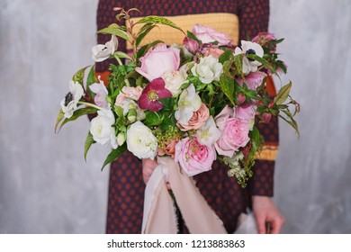 Young female florist holding a freshly made blooming floral bouquet of pastel carnations and eucalyptus against a gray wall.
