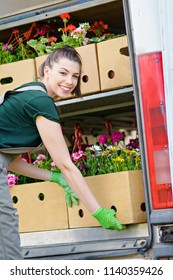 Young female florist packing boxes of flowers in a van. Solopreneur woman smiling, packing flowers for sale. Natural lighting, no retouch, closeup.