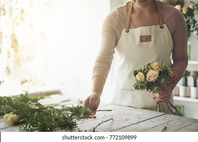 Young female florist preparing a bouquet of mixed flowers while standing at a table in her flower shop