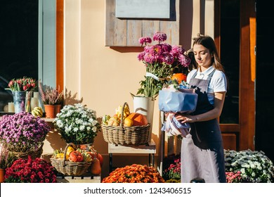 Young female florist seller of flowers and gifts shop waiting for customer on the threshold of her floral store with beautiful autumn decorations.