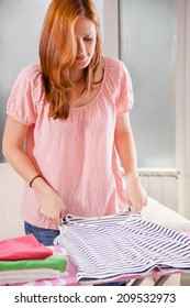Young Female Folding Clothes