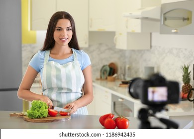 Young female food blogger recording video in kitchen