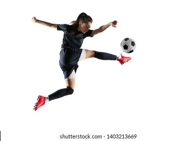 Young female football or soccer player with long hair in sportwear and boots kicking ball for the goal in jump isolated on white background. Concept of healthy lifestyle, professional sport, hobby.