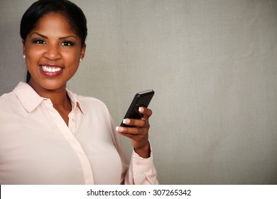 Young female in formal clothing holding a cellphone while smiling at the camera - copy space