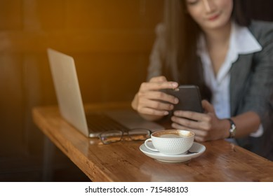 Young female freelancer checking email on cell during coffee break. Business concept.