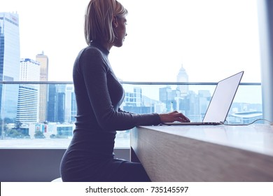 Young female freelancer sitting at the table with laptop computer. Business woman working on netbook in office interior