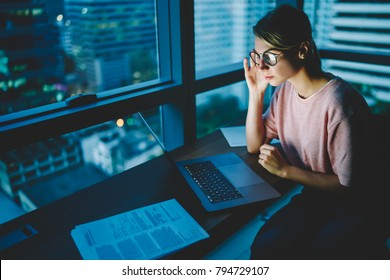 Young female freelancer in stylish eyeglasses watching training webinar on laptop computer connected to wireless internet.Pretty skilled female working on netbook  late at nigh while sitting in office