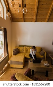 Young female freelancer in a white sweater is sitting on a living room couch in a beautiful and warm log cabin.