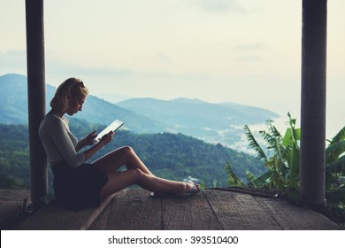 Young female freelancer is working in network via touch pad, while is sitting against beautiful view background with copy space for your advertising text message during her unforgettable trip in Asia