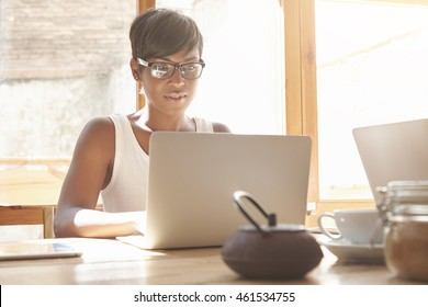 Young female freelancer working on laptop in cosy café. Good-looking dark-skinned woman with short hair and white top typing on computer in morning light. Productive job concept at comfy place.