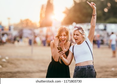 Young female friends having fun and using mobile phone
