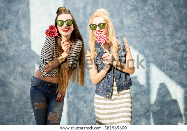 Young female friends having fun with candies standing on the blue wall background
