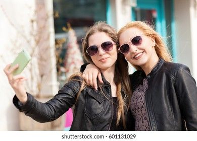 Young female friends taking a selfie outdoor in the city. Urban cool lifestyle