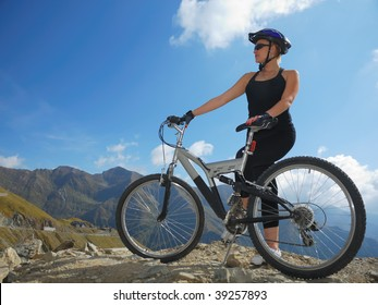 young female with full suspension bike looking at mountain landscape