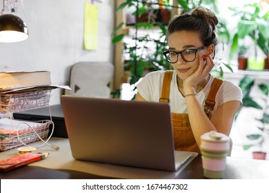 Young female gardener in glasses using laptop, communicates on internet with customer in home garden/greenhouse, reusable coffee/tea mug on table.Cozy office workplace, remote work, E learning concept