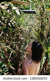 Young female getting shower outdoor in nature. Tropical bathroom, natural spa salon. Summer