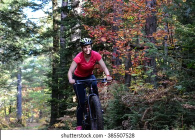 Young female girl mountain bike cycling on a trail in the woods