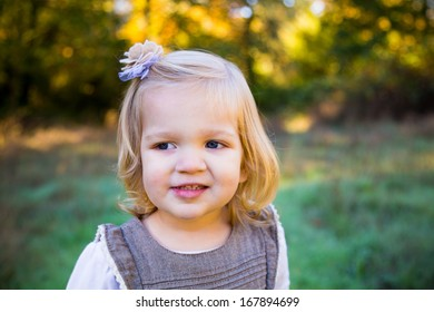 Young female girl outdoors for a natural light portrait in the fall with the child looking happy and having a good time.
