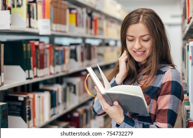 Young female girl  student smiling with book in library