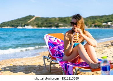 Young female girl woman hand holding a frappe or ice coffee at the beach in swimsuit bikini while relaxing in a sunbed at vacation in sunny day drinking by the sea