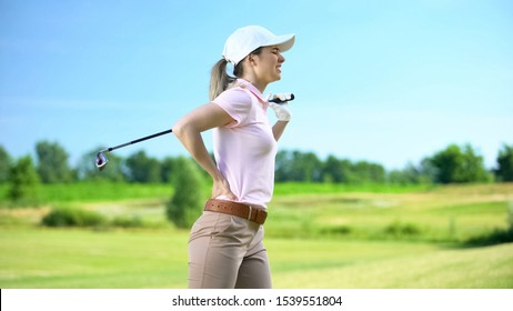 Young female golfer with club feeling lower back pain after shot, sports trauma