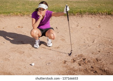 Young female golfer frustrated and stuck in a sand trap