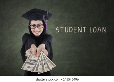 Young female graduate getting money from student loan with blackboard background