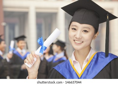 Young Female Graduate Holding Diploma, Portrait