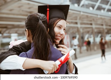 young female graduate hugging her mother at graduation ceremony. students in the graduation day are holding certificate and flower bouquet in hand